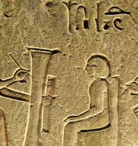 Ancient Egyptian Scribe writing Hieroglyphs with students.