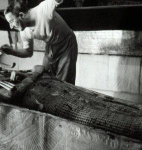 Howard Carter brushing dust off King Tut's mummy.