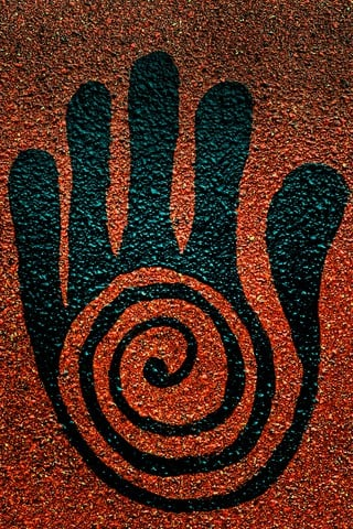 Depiction of healer's hand created in pebbles.
